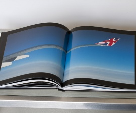 A photo from the book showing the wing of a plane high above the clouds